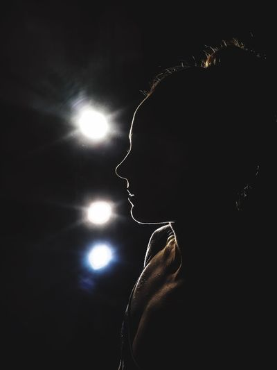 Portrait of woman with illuminated lights at night