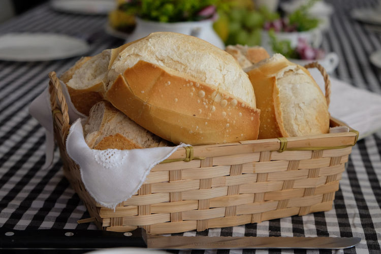 Close-up of homemade breads in whicker basket on table