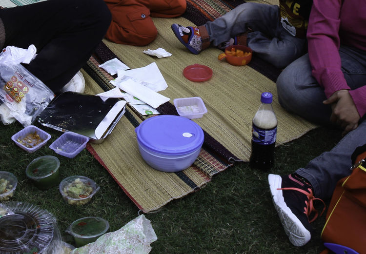 Adults and children sitting around a coit mat, with the aftermath of a picnic. There are various plastic cups and other utensils, carrying the remains of snacks along with a plastic container, along with a cold drink bottle. Shoes and sandals are visible as well along with a bag. Adult Coir Matting Cold Drink Day Drink Food Food Container Food Containers Food Finished High Angle View Human Hand People People Sitting Picnic Plastic Containers Plastic Cup Real People Relaxing Sitting
