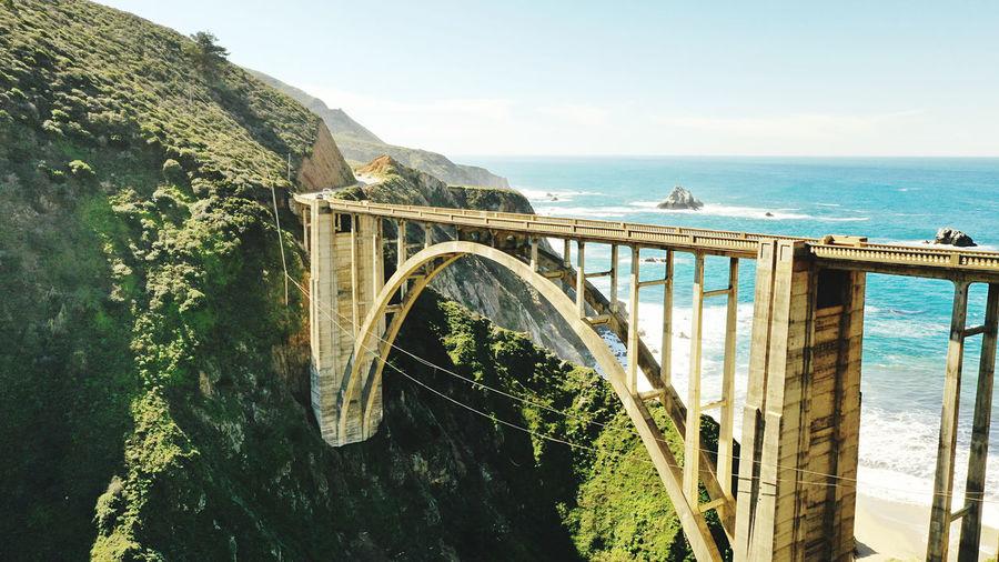 Arch bridge over sea against sky