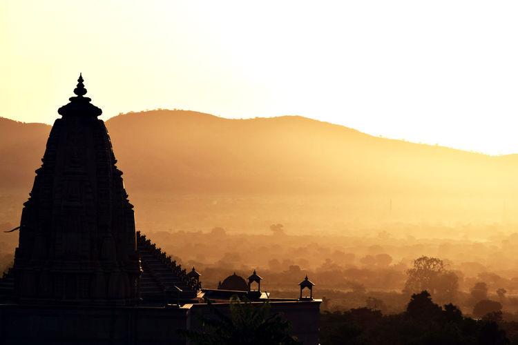 Silhouette nareli jain temple against sky at sunrise