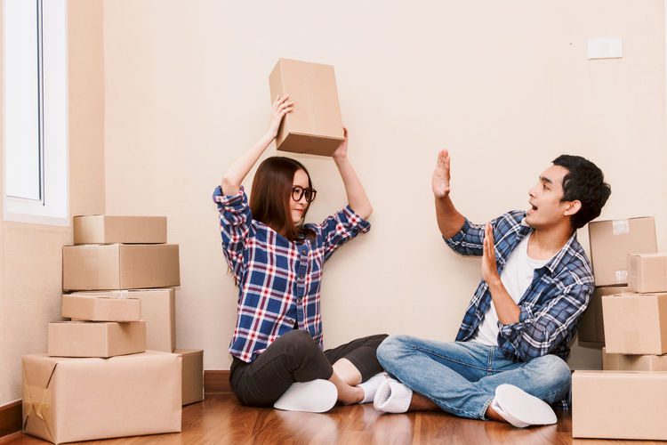 Young couple with cardboard box at home - Business online and delivery concept Adult Beginnings Box Box - Container Cardboard Cardboard Box Casual Clothing Change Container Couple - Relationship Emotion Flooring Happiness Home Ownership Indoors  Moving House Packing Relocation Sitting Togetherness Two People Unpacking Women Young Adult Young Women