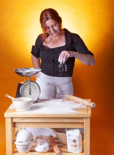 Woman preparing food standing by orange background