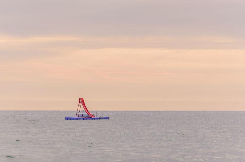 Slide On Diving Platform In Sea Against Sky During Sunset