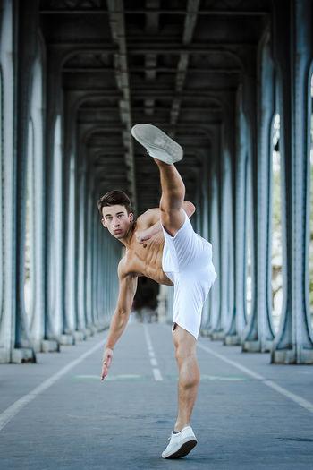 Portrait of young man kicking under bridge