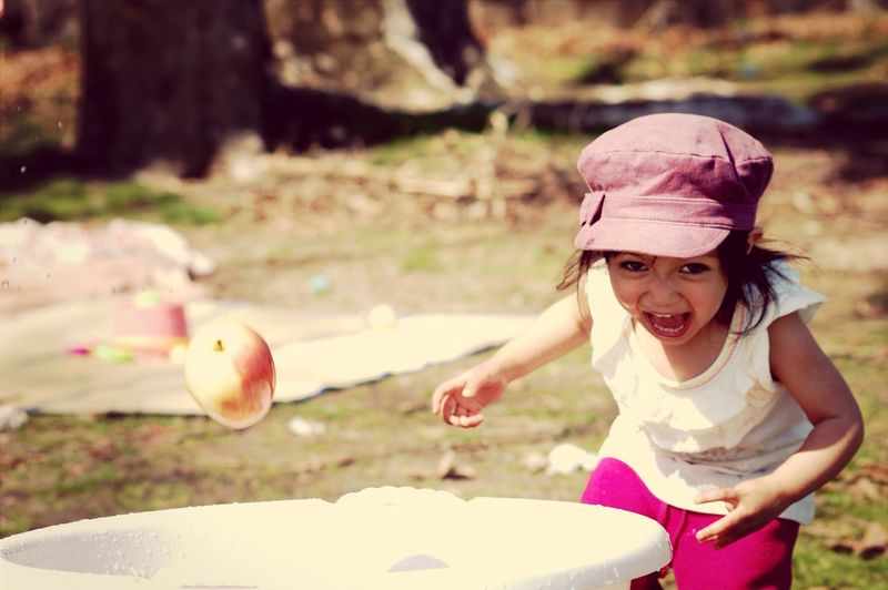 Portrait Of Playful Girl Throwing Apple In Tub While Screaming At Park