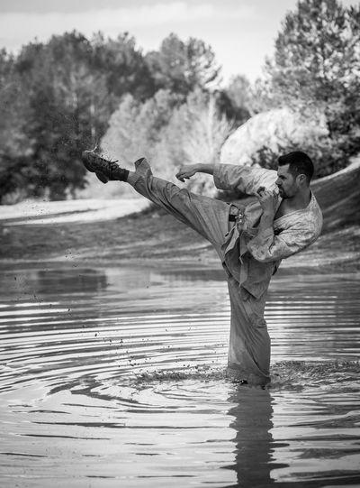 Man Kicking In Lake Against Trees
