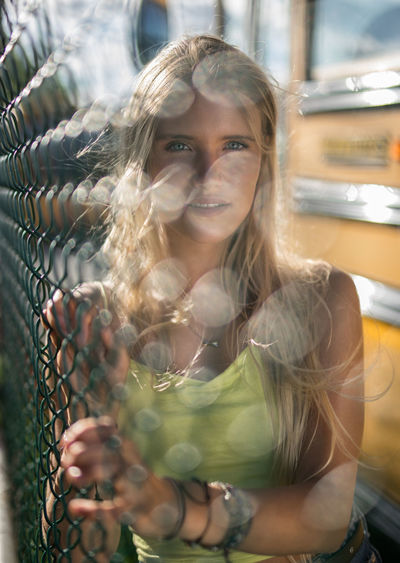 Portrait of young woman seen through fence