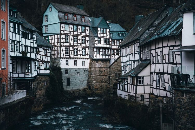 Moody winter scene from monschau germany with historic half timbered buildings lining the river.