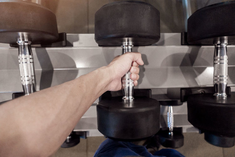 Cropped Hand Lifting Dumbbell At Gym