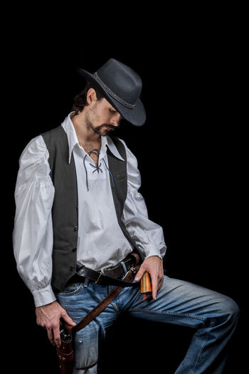 Handsome young man. This is an American cowboy. A vow to a white shirt, brown waistcoat and blue jeans. Black shoes on the feet. Carries a shtyapa, on a belt two pistols. The hair is of medium length; on the face is a beard and mustache. Authentic photo. Culture of America. Cowboy Wild West America American Gun National Authentic Moments Lifestyles Lifestyle One Person Candid Authentic Hat Three Quarter Length Clothing Men Black Background Front View Males  Adult Young Men Holding Real People Young Adult Mid Adult