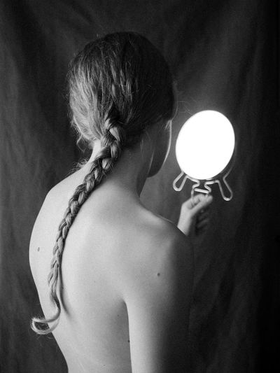 Black and white view of a young beautiful woman holding a mirror with no reflection.