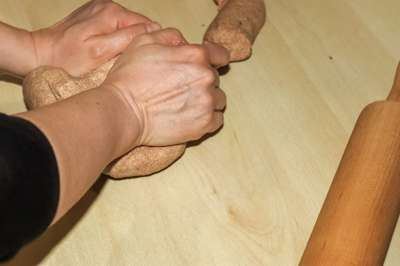 Close-up of man holding hands at home