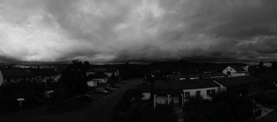 Buildings in town against cloudy sky