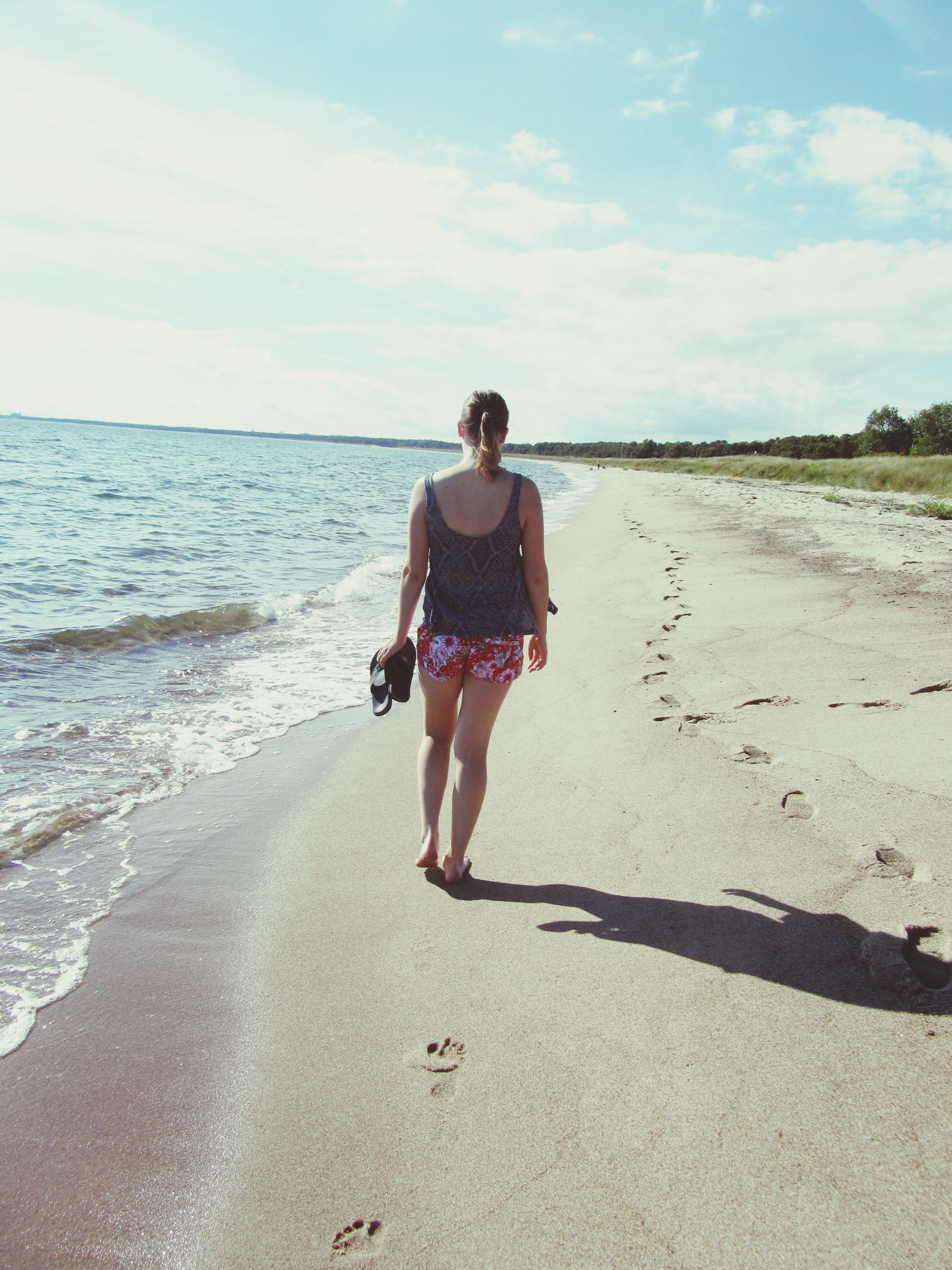 beach, full length, sea, sunlight, vacations, sand, water, sky, shadow, walking, shore, leisure activity, summer, person, cloud - sky, casual clothing, sunny, tourism, scenics, day, tourist, young adult, weekend activities, tranquil scene, nature, beauty in nature, outdoors, confidence, tranquility