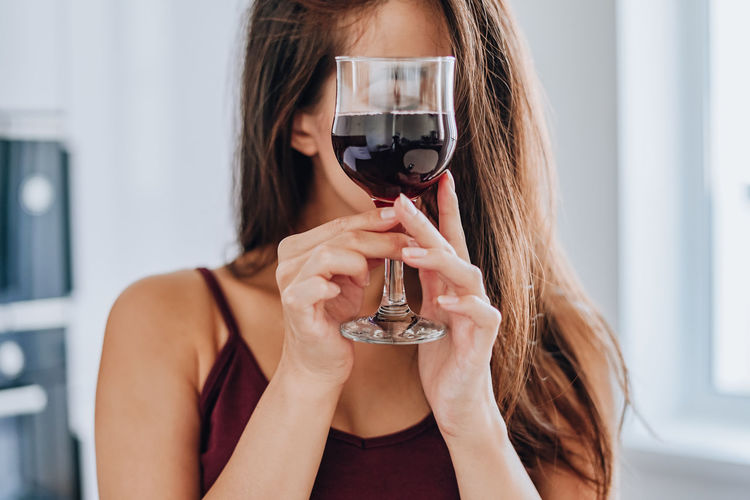 Full length portrait of woman holding glass