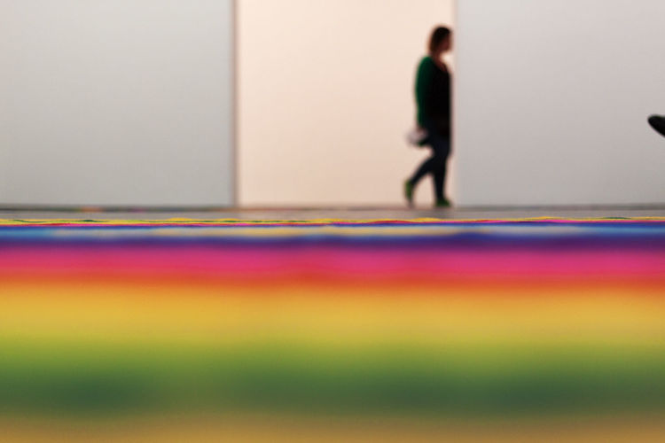 Blurred motion of people standing on multi colored floor