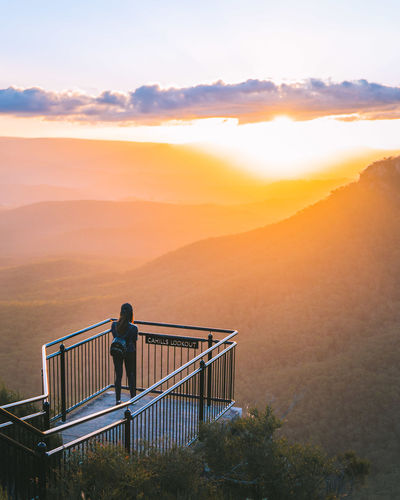 High angle view of woman standing at observation point during sunset