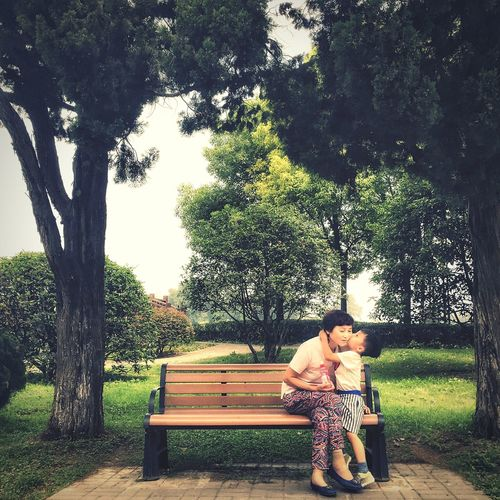 Accompany each other. Tree Two People Young Adult Sitting Togetherness Park - Man Made Space Women Young Women Happiness Love Smiling Green Color Adult Nature Cheerful Lifestyles Outdoors Couple - Relationship Relaxation Day Live For The Story