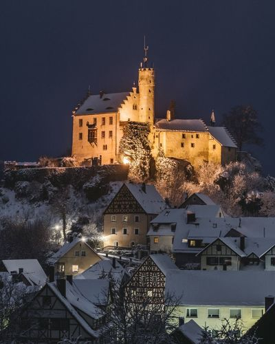 Illuminated buildings in city against sky during winter