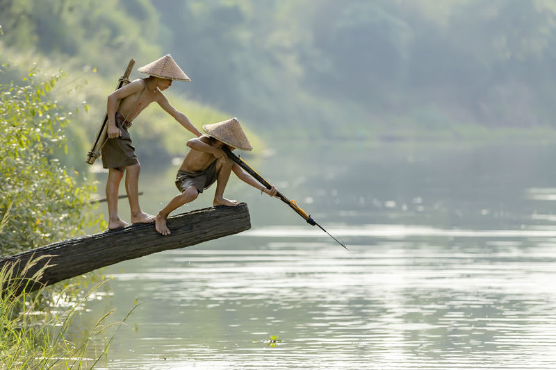 Traditional fishing on lake against plants