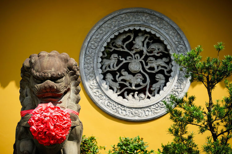 Low angle view of statue against red wall
