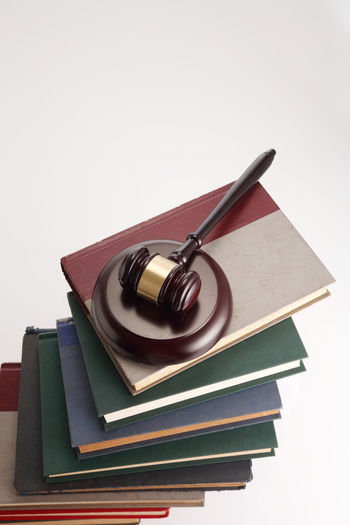 Close-Up Of Gavel On Stacked Books Against White Background