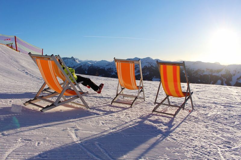 Deck chairs on snowcapped mountain against sky during sunny day