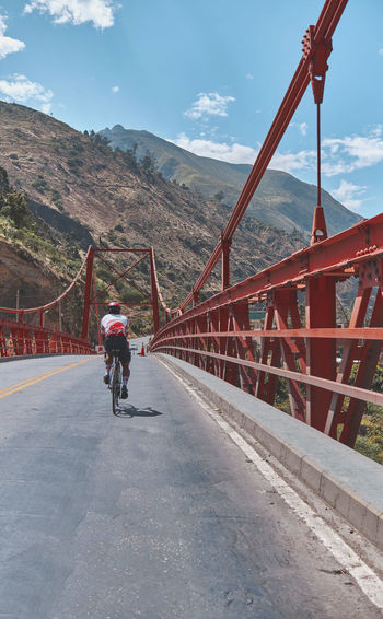 Rear view of man riding bicycle on bridge against sky