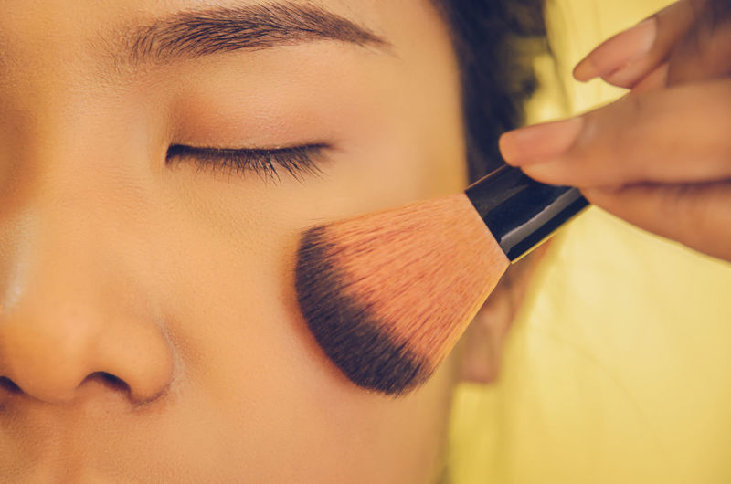 Close-up of young woman applying face powder against yellow background