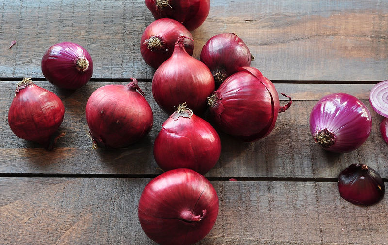 Red Onions on wooden table Abundance Arrangement Backgrounds Close-up Color Image Composition Directly Above Food Food And Drink Full Frame Healthy Eating Horizontal Indoors  Large Group Of Objects No People Onion Organic Purple Red Ripe Still Life Variation