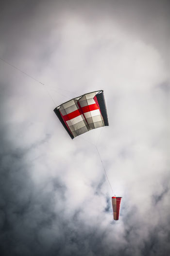 Low angle view of kite flying against cloudy sky