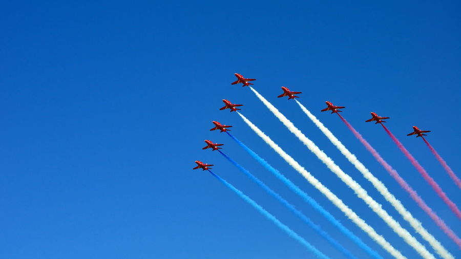 Low Angle View Of Air Show Against Clear Blue Sky