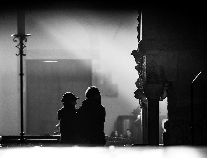 Rear view of silhouette man and woman standing at home
