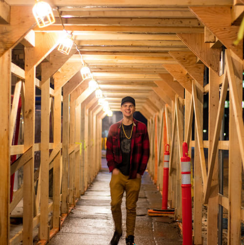 Portrait of teenager boy walking in illuminated wooden covered walkway