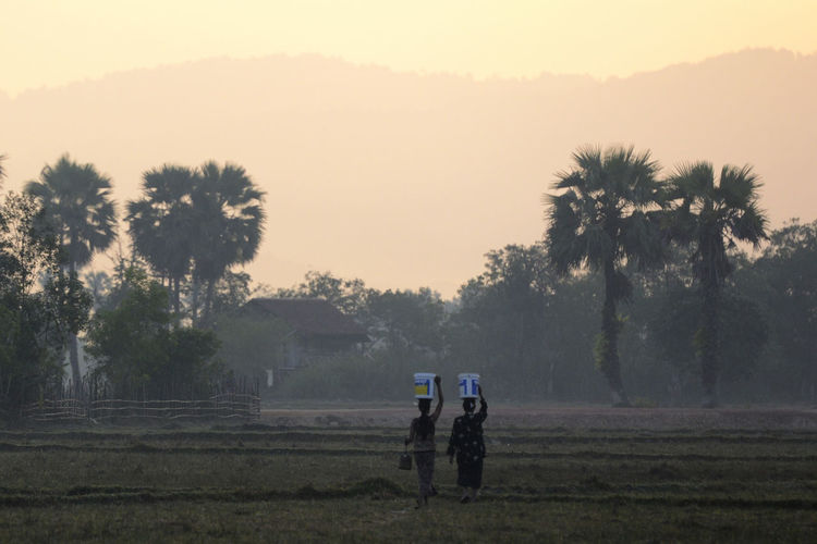 Rear view of women walking with bucket on head during sunset