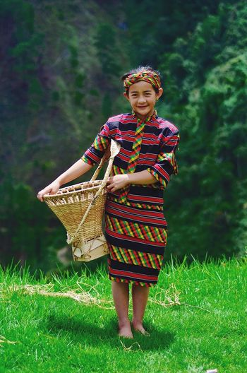 Portrait of smiling young woman in basket on field