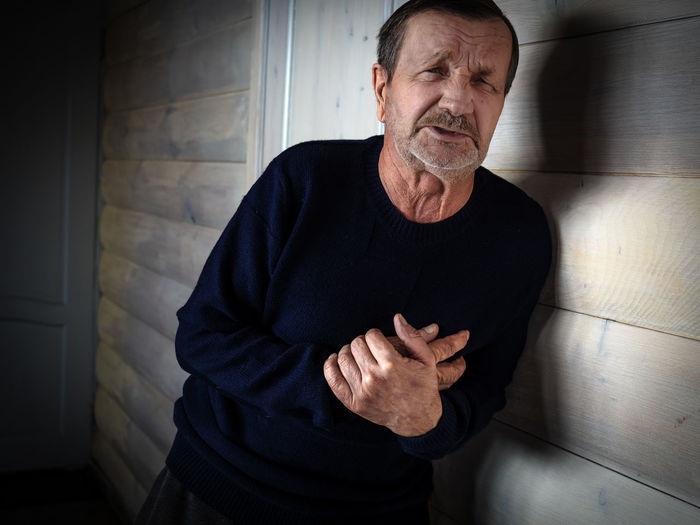 Portrait of man with chest pain by wall at home