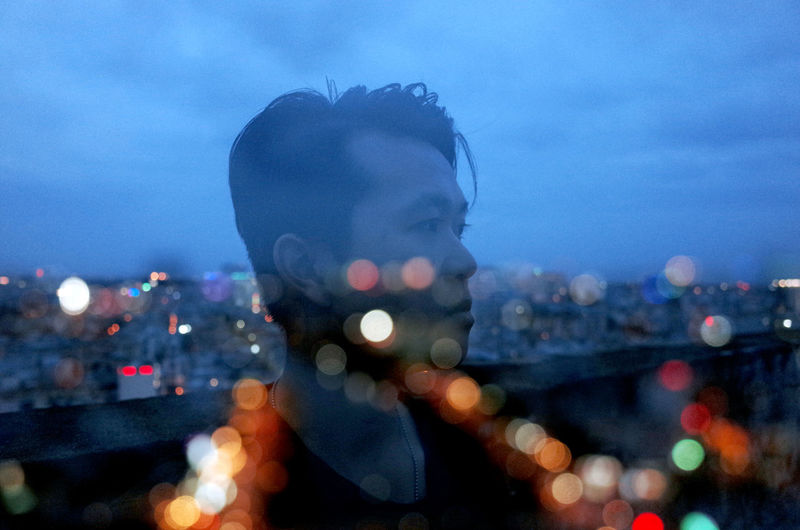 Portrait of man in city against sky at night