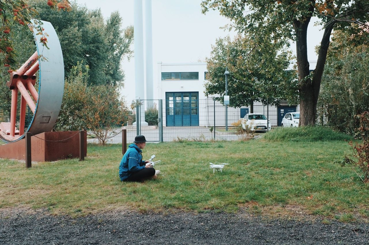 BOY SITTING IN FRONT OF BUILDING
