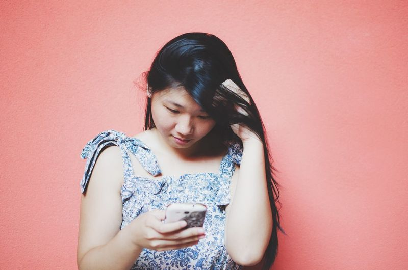 EyeEm Selects Mobile Phone Text Messaging Wireless Technology Smart Phone Communication Portable Information Device Looking Down Technology Connection Holding One Person Colored Background Front View Young Adult Indoors  Real People Young Women Day Adult People Addiction
