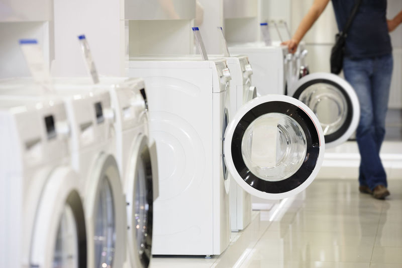Low section of man standing by washing machine at laundromat