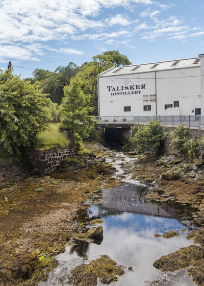 Talisker Distillery, Carbost, Isle of Skye, Scotland Carbost Day Distillery Distillery Tour Isle Of Skye Landscape Landscape_Collection Landscape_photography Nature No People Outdoors Sky Talisker Talisker Distillery Tree Tree Water Water Reflections Water_collection