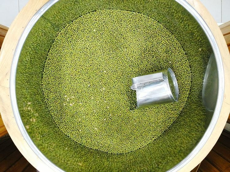 Whole green mung dal for sale in container at Big Bazaar. Gourmet Mung Dal Moong Dal Mung Bean Mung Moong Dal Cereal Pulses Sale Container Top View Circular Round Background Healthy Protein Food Seeds Vegetarian Market Supermarket Big Bazaar Lentils Fresh