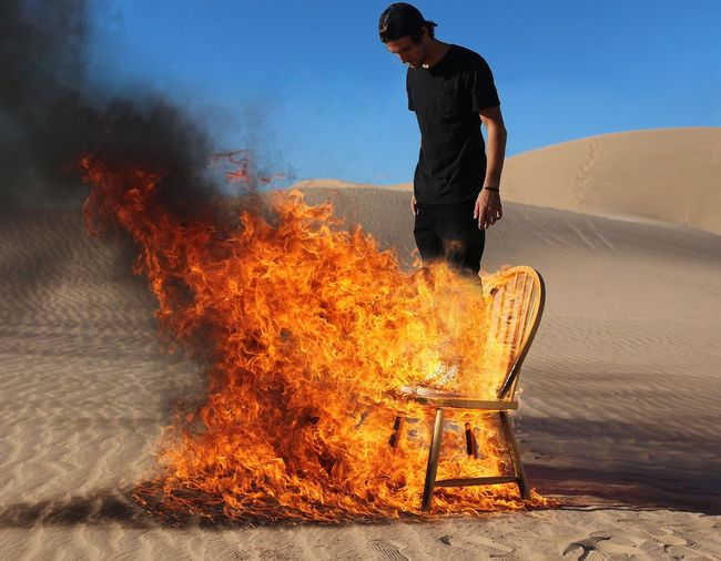Young man standing on burning chair at desert