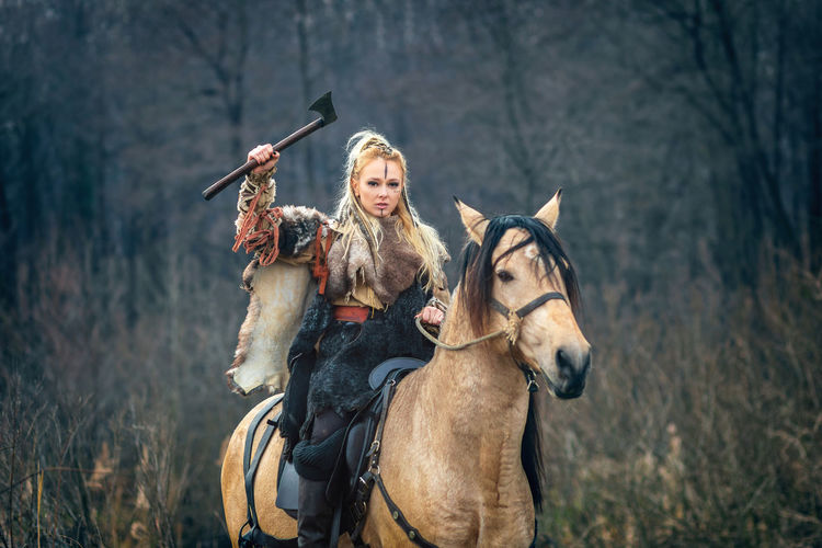 Portrait Of Woman With Hand Tool Riding Horse In Forest
