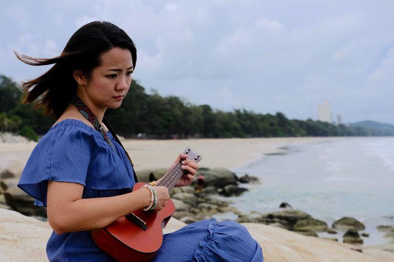 Beautiful woman sitting on beach against sky