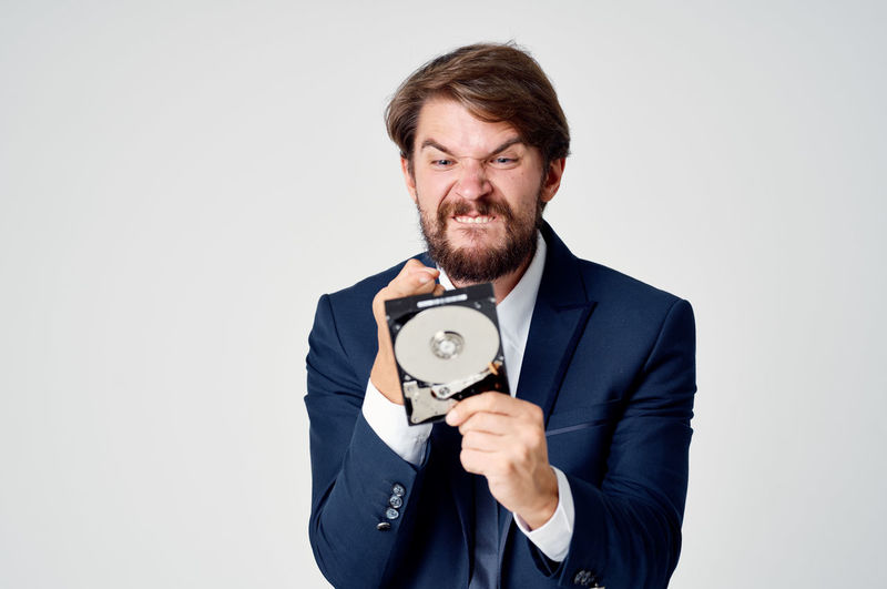 Portrait of man holding camera over white background