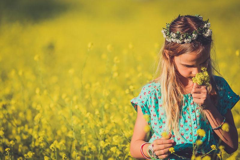 Girl Smelling Flowers On Field