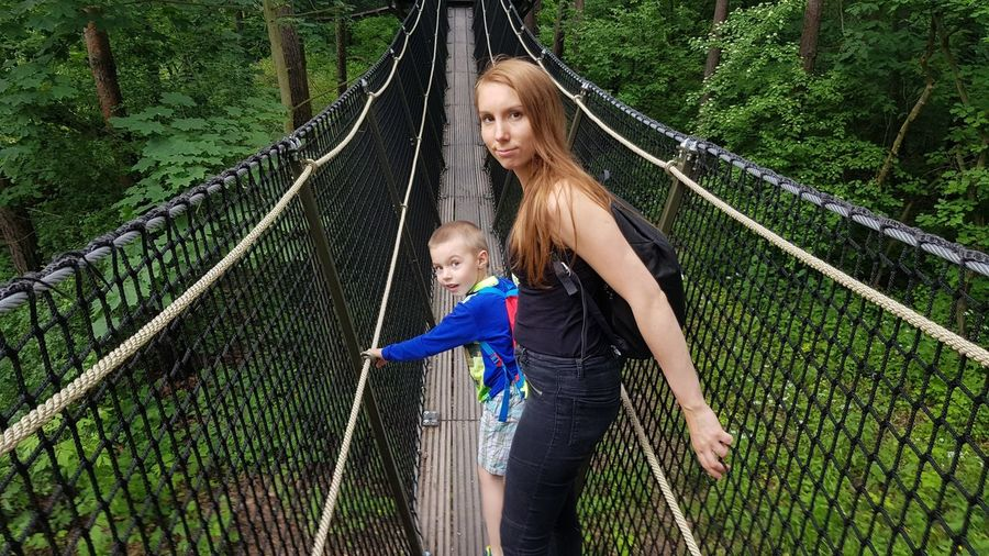 Portrait of mother with son standing on footbridge